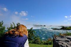 Mujer pelirroja vista el apuntar de su cámara al Niagara Falls famoso, Ontario, Canadá foto de archivo libre de regalías