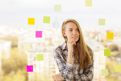 Mujer pensativa al lado de etiquetas engomadas Imagen de archivo libre de regalías
