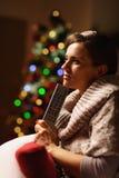 Mujer pensativa con el árbol de navidad cercano teledirigido de la TV Imagen de archivo libre de regalías