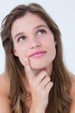 Mujer pensativa con el finger en la barbilla Foto de archivo libre de regalías