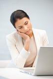 Mujer pensativa con el ordenador portátil Fotografía de archivo