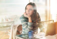 Mujer pensativa con el ordenador portátil Fotos de archivo