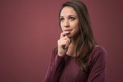 Mujer pensativa con la mano en la barbilla Fotos de archivo libres de regalías
