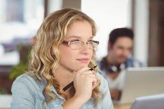 Mujer pensativa con la mano en la barbilla mientras que colegas que trabajan en fondo Foto de archivo