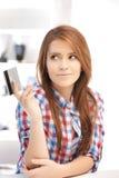 Mujer pensativa con la tarjeta de crédito Imágenes de archivo libres de regalías
