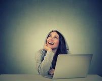 Mujer pensativa con un ordenador portátil que mira para arriba que sueña despierto Imagen de archivo libre de regalías