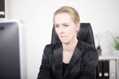 Mujer pensativa de la oficina que mira la pantalla de ordenador imagen de archivo libre de regalías