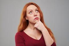 Mujer pensativa del pelirrojo que mira hacia arriba a un espacio de la copia Imagen de archivo libre de regalías