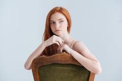 Mujer pensativa del pelirrojo que se sienta en la silla y que mira lejos Foto de archivo