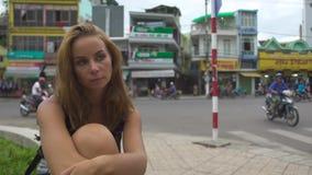 Mujer pensativa del retrato que se sienta en fondo del tráfico de la calle y de coche de la ciudad Haga frente a la muchacha pens metrajes