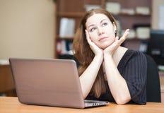 Mujer pensativa un brunette que piensa en la tabla Fotos de archivo libres de regalías