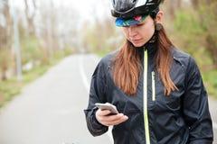 Mujer pensativa en casco de la bicicleta usando el teléfono celular Imágenes de archivo libres de regalías