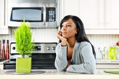 Mujer pensativa en cocina Imagen de archivo