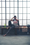 Mujer pensativa en el engranaje del entrenamiento que descansa sobre banco en gimnasio del desván Fotografía de archivo