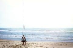 Mujer pensativa en la playa que mira en la distancia Foto de archivo