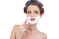Mujer pensativa en los bigudíes de pelo que presentan con la maquinilla de afeitar Fotografía de archivo