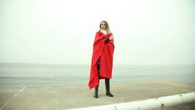 Mujer pensativa en manta roja en la orilla de mar almacen de video