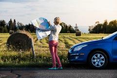 Mujer pensativa en una escena rural que mira un mapa Fotografía de archivo libre de regalías