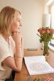 Mujer pensativa en una tabla con el libro de colorear adulto Imágenes de archivo libres de regalías