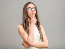 Mujer pensativa en vidrios Foto de archivo libre de regalías