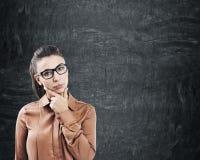 Mujer pensativa en vidrios cerca de una pizarra Fotos de archivo libres de regalías