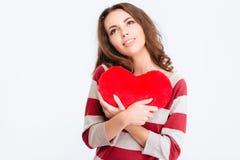 Mujer pensativa feliz que lleva a cabo el corazón rojo y que mira para arriba Imagen de archivo