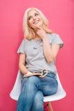 Mujer pensativa feliz que se sienta en la silla con la revista Imagenes de archivo