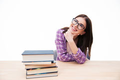 Mujer pensativa feliz que se sienta en la tabla con los libros Fotografía de archivo libre de regalías