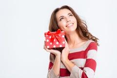 Mujer pensativa feliz que sostiene la caja de regalo y que mira para arriba Imagen de archivo libre de regalías