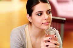 Mujer pensativa hermosa joven que se sostiene de cristal con agua Imágenes de archivo libres de regalías