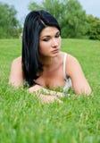 Mujer pensativa hermosa que miente en hierba imagen de archivo