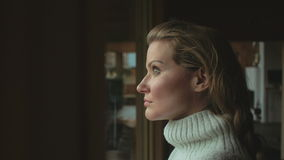 Mujer pensativa hermosa que mira a través de una ventana almacen de video