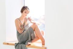 Mujer pensativa hermosa que se sienta en ventana-travesaño y el café de consumición Fotografía de archivo libre de regalías