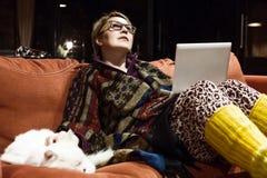 Mujer pensativa interior casera acogedora que usa el ordenador que juega con el gato fotografía de archivo libre de regalías