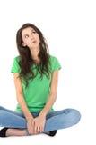 Mujer pensativa joven aislada que se sienta con las piernas cruzadas. Imagenes de archivo