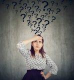 Mujer pensativa joven con demasiadas preguntas imagen de archivo libre de regalías