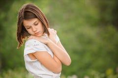 Mujer pensativa joven con las manos dobladas contra Foto de archivo libre de regalías