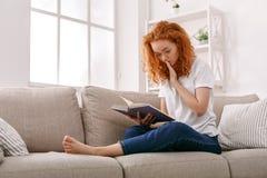 Mujer pensativa joven con un libro Imagenes de archivo