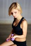 Mujer pensativa joven del ajuste que hace entrenamiento con pesa de gimnasia Fotografía de archivo