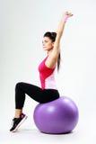 Mujer pensativa joven del deporte que estira en fitball Foto de archivo libre de regalías