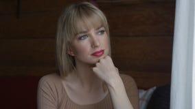 Mujer pensativa joven que mira a través de una ventana Fotos de archivo libres de regalías
