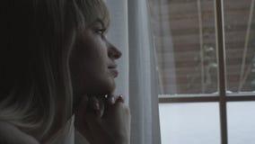 Mujer pensativa joven que mira a través de una ventana Fotografía de archivo libre de regalías