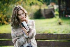 Mujer pensativa joven que se relaja en banco de parque Fotos de archivo