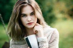 Mujer pensativa joven que se relaja en banco de parque Fotografía de archivo