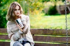 Mujer pensativa joven que se relaja en banco de parque Imágenes de archivo libres de regalías