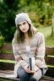 Mujer pensativa joven que se relaja en banco de parque Imagen de archivo libre de regalías