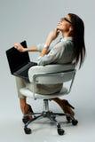 Mujer pensativa joven que se sienta con el ordenador portátil y que mira para arriba Foto de archivo libre de regalías