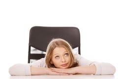 Mujer pensativa joven que se sienta en el escritorio Foto de archivo libre de regalías