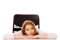 Mujer pensativa joven que se sienta en el escritorio Imagen de archivo