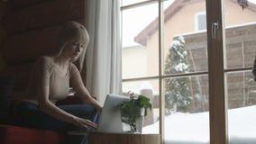 Mujer pensativa joven que se sienta en el sofá mientras que mecanografía y lee correos electrónicos en el ordenador portátil con  Imágenes de archivo libres de regalías